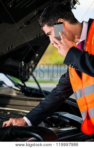 Man with car engine problems or breakdown calling repair service hotline