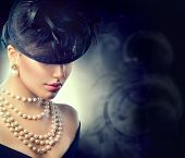 Retro Woman Portrait. Vintage Style Girl Wearing Old fashioned Hat, pearls necklace and earrings, retro Hairstyle and Make-up. Romantic lady over black background. Pearl Jewellery poster