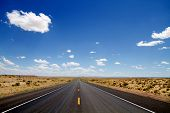 Empty desert road stretching to horizon poster