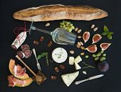 Wine and snack set. Baguette, glass of white, figs, grapes, nuts, cheese variety, meat appetizers and herbs on black grunge background, top view poster
