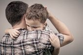 sad son hugging his dad near wall at the day time poster