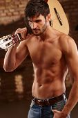 Sexy latin lover holding guitar with bare upper body. poster