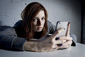 young sad vulnerable girl using mobile phone scared and desperate suffering online abuse cyberbullying being stalked and harassed in teenager cyber bullying concept poster