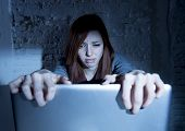 sad and scared female teenager with computer laptop suffering cyberbullying and harassment being online abused by stalker or gossip feeling desperate and humiliated in cyber bullying concept poster