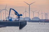 Hydraulic Harbor Crane in the port of Eemshaven with oil tanks in background under setting sun poster