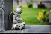 Cherub angel statue with wings carved from granite stone religious symbol brining hope and love poster