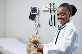 Girl doctor using stethoscope on teddy bear