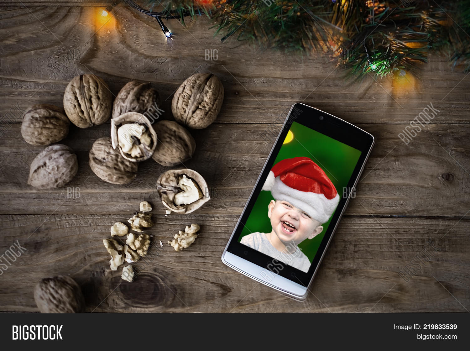 391ef0136e2e7 Mobil phone with a portrait of cute laughing baby in a red Santa Claus hat
