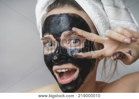 Happy joyful woman applying black mask on face. Skin care, clean pores, exfoliation