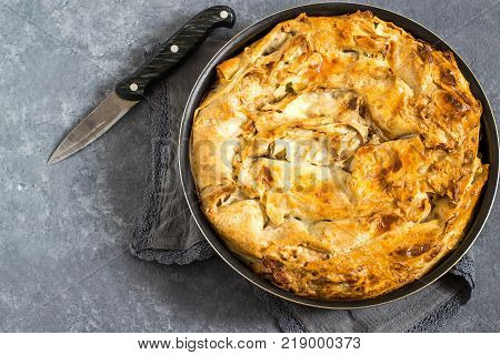 Simple homemade pie made of puff pastry with cheese and herbs. Pan with pie on gray napkin and knife on gray concrete background. Rustic style. Top view