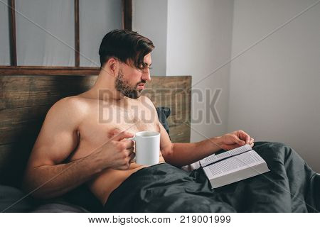 Handsome man reading an exciting book while holding a cup of hot tea or coffee being in his bedroom. It is morning time. Closer view.