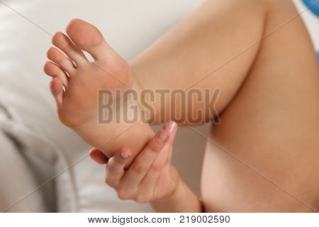 Close-up on the foot fingers. Attractive slender tanned female body part.
