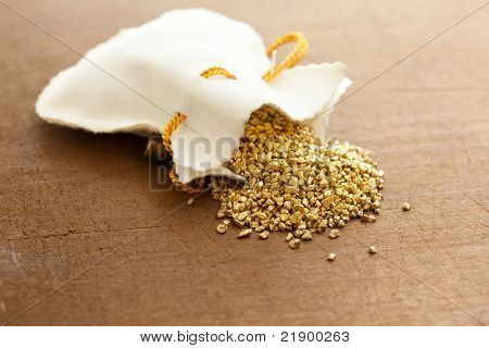 gold nuggets spilling out from a small pouch.