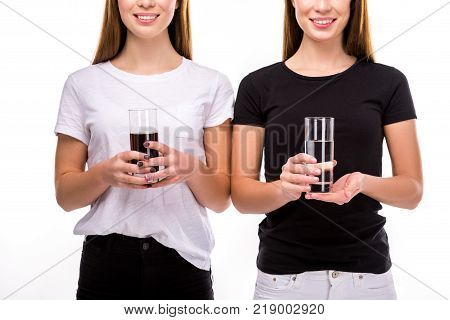 partial view of smiling women holding glasses of soda and water in hands isolated on white