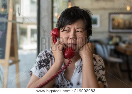 Asian Woman Waiting In Coffee Shop Cafe With Clock