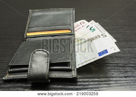 Euro banknotes ejected from a black wallet.