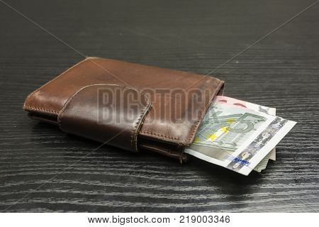 Euro banknotes ejected from a brown wallet.