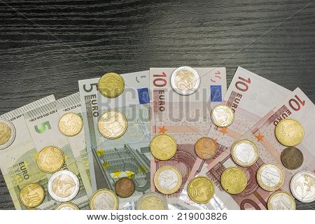 Euro coins and banknotes of various denominations on a wooden table.