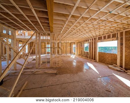 New house interior construction framing with exposed wooden studs and flooring