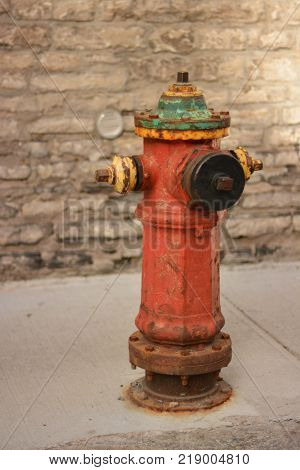 A vintage red metallic fire hydrant in the ground for fighting urban fires.
