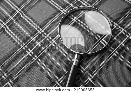 Magnifying glass on a plaid background black and white frame