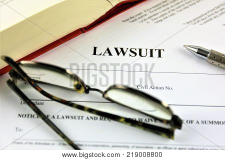 An concept Image of a lawsuit with pen, glass and book