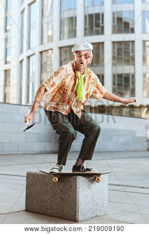 Grandpa on a skateboard jumps from a high stone.