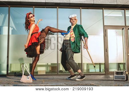 Pensioner with a walking stick in his hand dancing with a young woman in the street.