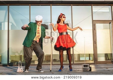 An old man and a woman dancing in the street is a fast dance the grandfather is leaning on a cane for walking.