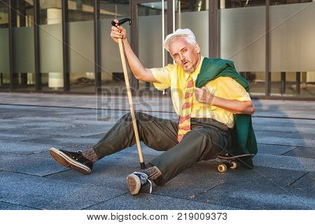 Pensioner is tiredly sitting on the skateboard in his hand a walking stick.
