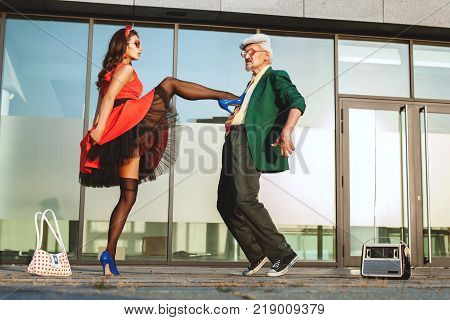 Retired and a young woman dancing fast dance on the street.