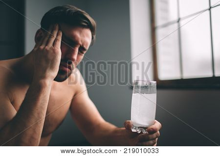 Sad guy suffering from hangover in morning. Naked bearded dark-hair sleepy young man holding a glass of water poster