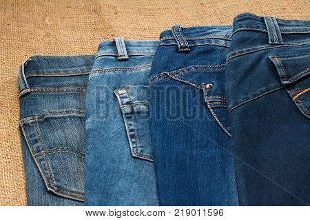 Two pair of jeans. View of top parts of folded jeans lying on sackcloth
