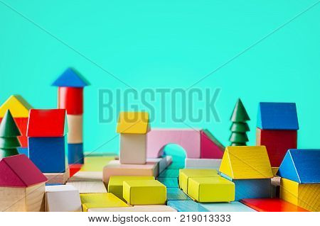 Toy wooden house from coloured blocks on blue background. Building construction concept. Real estate constructing a house from a wooden cubes on desk.
