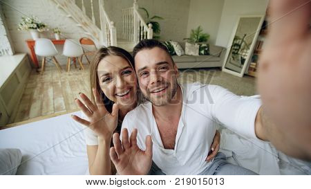 Young cute and loving couple having video chat holding tablet computer camera and chatting to friends sitting in bed at home