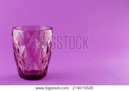 Part Of Purple Color Drinking Glass On Bright Purple Background