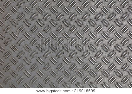 Dark gray industrial anti slip embossed metal steel plate with double diagonal bumps of diamond pattern texture background close up