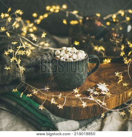 Christmas or New Year winter hot chocolate with marshmallows in mug over wooden board served in bed with holiday light garland, blanket and gray sweater, selective focus, copy space, square crop