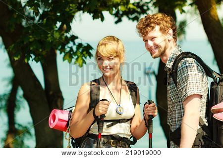 Two young people tourists hiking by sea ocean water. Backpackers couple on summer vacation trip journey. Woman with trekking poles sticks.