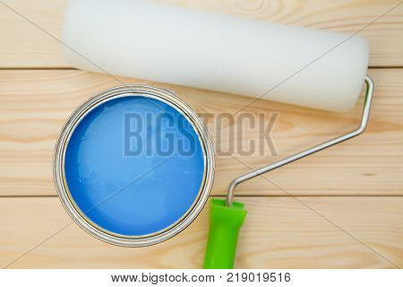 A can of blue oil paint and a clean paint roller on a light uncolored wooden background. Close up. Top view. Space for your text or pruduct display.