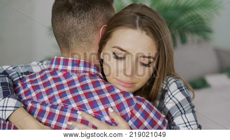 Closeup of young upset couple embrace each other after quarrel. Woman looking wistful and sad hugs her boyfrined at home