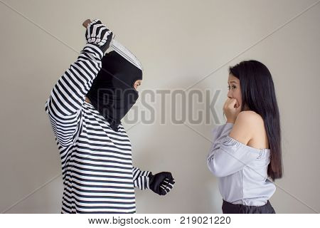 Robbery make a scared young Asian victim to walk alone in a lonely alley/Hostage of terrorist or burglar threatening with knife ,criminal concept