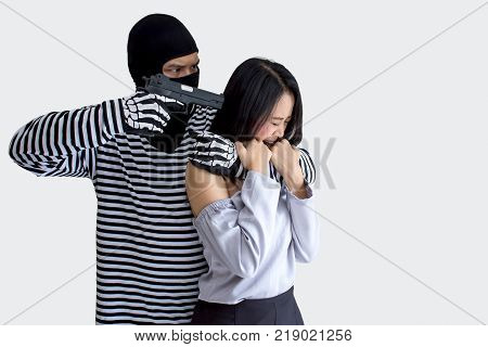 Robbery make a scared young Asian victim to walk alone in a lonely alley/Hostage of terrorist or burglar threatening with gun isolated on a white background,criminal concept
