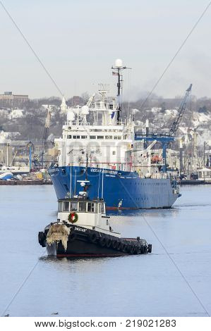 New Bedford Massachusetts USA - December 15 2017: Tug Jaguar and research vessel Ocean Researcher on Acushnet River with New Bedford backdrop (vertical format)
