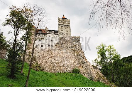 Bran or Dracula Castle in Transylvania, Romania. The castle is located on top of a mountain under a gloomy cloudy sky