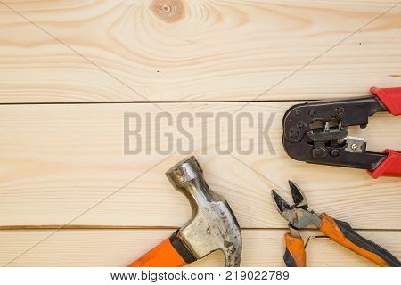 Repairing and construction concept. A set of repair tools- a hammer and pilers on a light uncolored wooden background. Top view. Space for your text or pruduct display.
