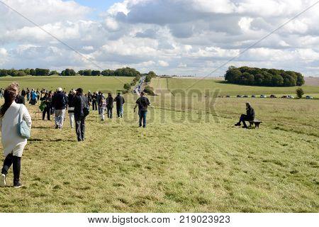 STONEHENGE, UK - SEPTEMBER 22, 2017: Visitors walking around Stonehenge, with heavy traffic and long delays on the A303 Stonehenge, Amesbury, Wiltshire, England, UK