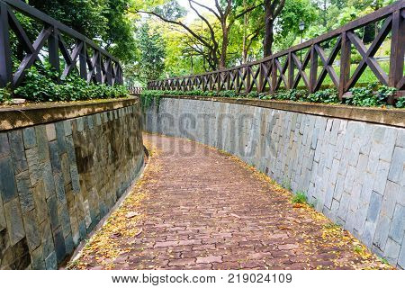 redbrick pathway or footpath with big stone wall in sunny day. underground crossing at fort canning public parksingapore. travel concept.