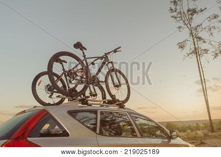 Passanger Car With Two Bicycle Mounted To The Roof. Sunset.