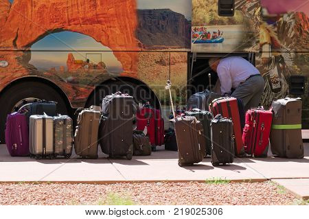 Zion Park Utah USA - June 03 2015: Tourists' luggage ready to be boarded at the bus departure. Traveling trip in the state of Utah. In the background Delicate Arch.